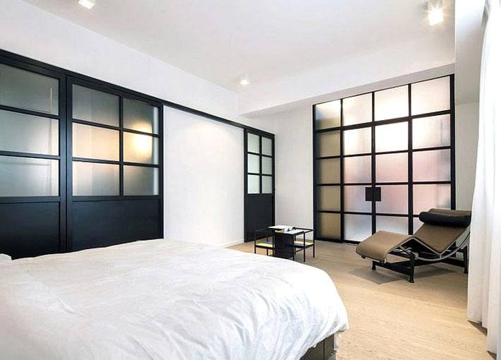 минимализм в спальне с белыми стенами и черной дверью