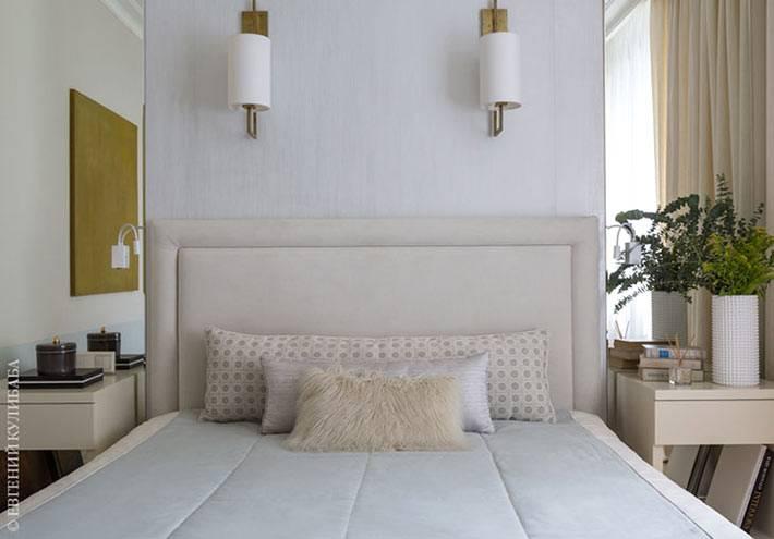 большая кровать с мягким изголовьем в маленькой спальне