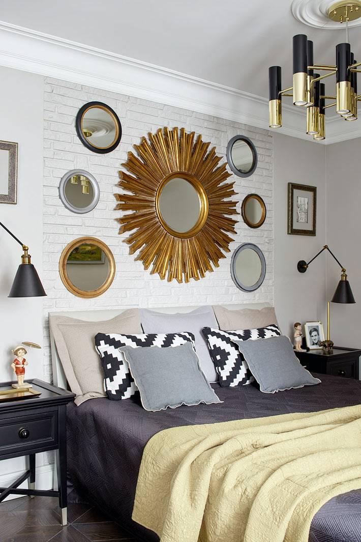 большое зеркало-солнце с маленькими зеркалами вокруг над кроватью