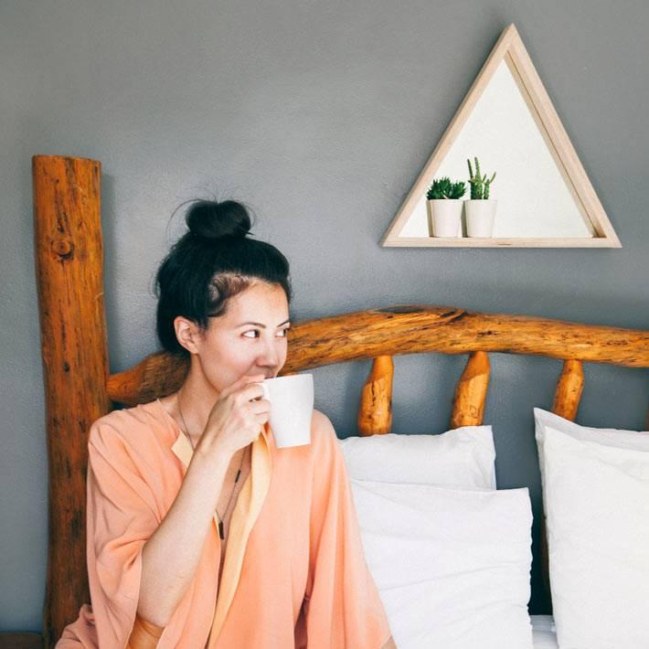 кровать из деревянных веток и маленькая полка с зеркалом