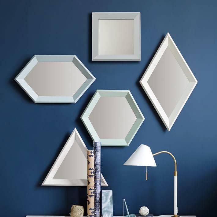 зеркала разной геометрической фомы в белых рамах на синей стене фото