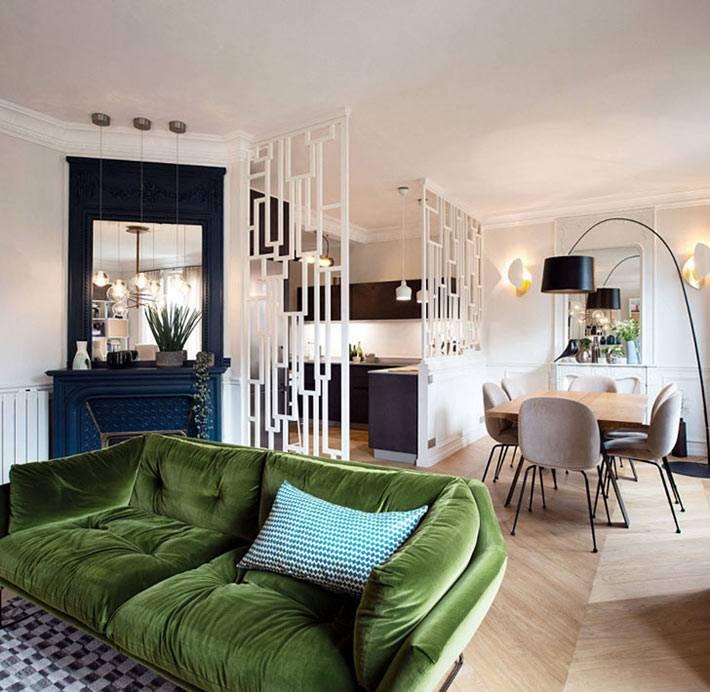 квартира-студия с белой перегородкой и зеленым диваном