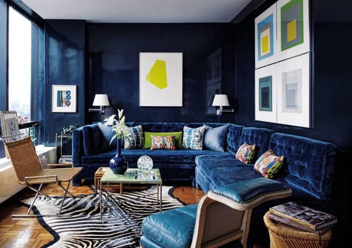 насыщенный синий цвет стен и вельветовый диван в комнате