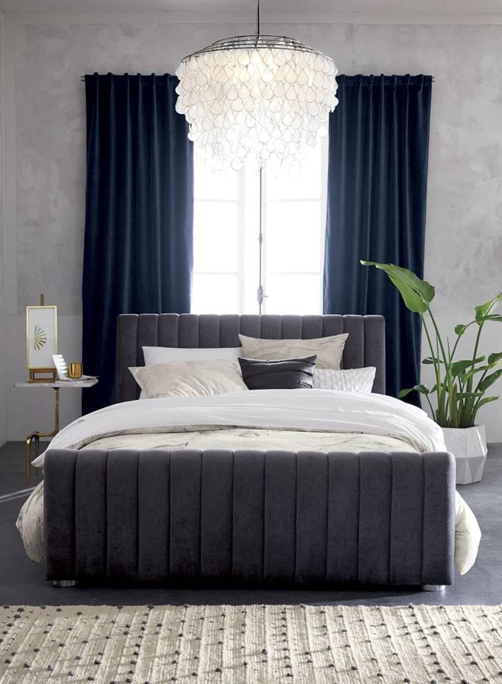 вельветовая оббивка кровати хорошо сочетается с синим шторами