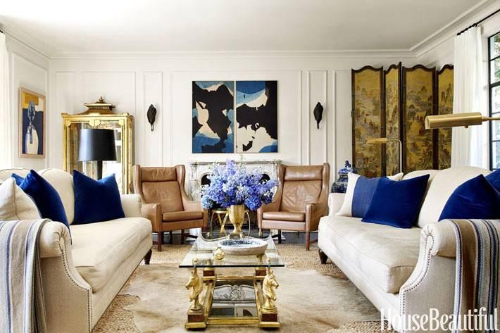 красивая расписная ширма и золотые детали в дизайне гостиной