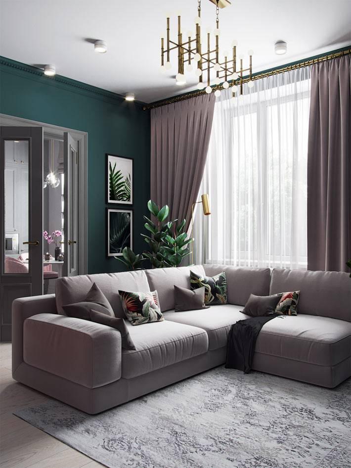 гостиная комната с изумрудными стенами и угловым диваном