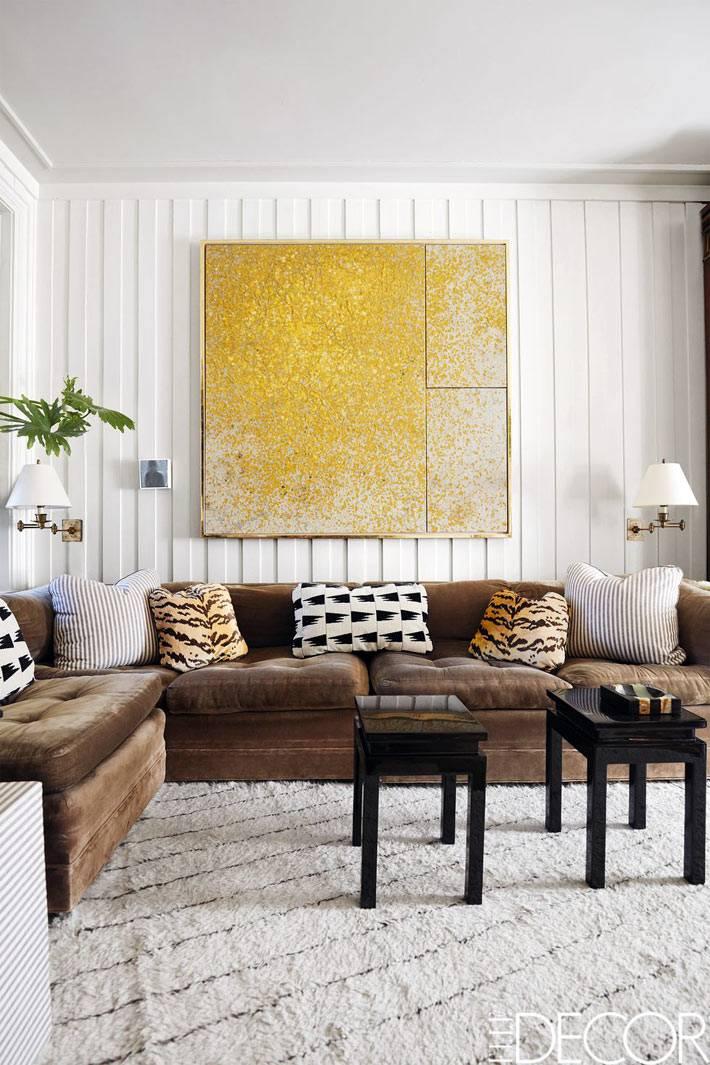 желтая картина и коричневый кожанный диван в белом интерьере