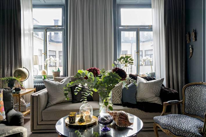 светлый диван с подушками в темном интерьере квартиры