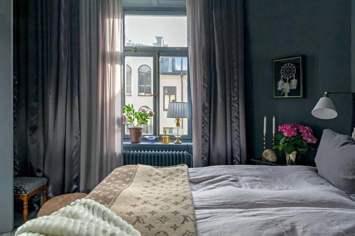 уютный интерьер темной спальни с двойными шторами