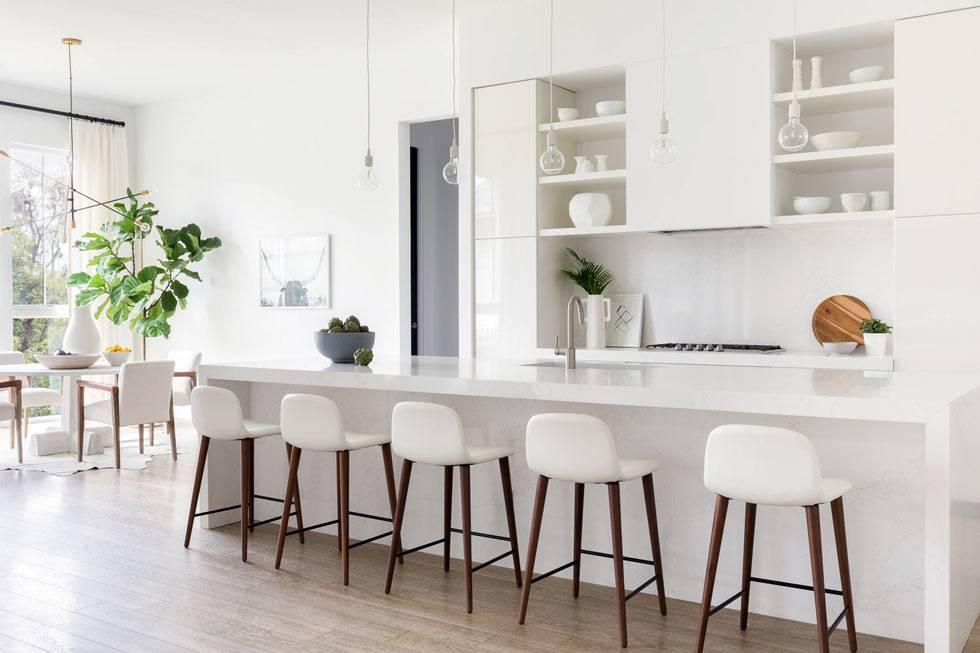 кухонная зона с длинным белым столом-барной стойкой