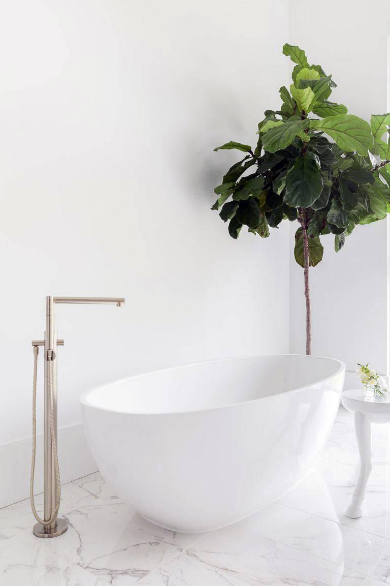овальная чаша ванны на мраморном полу в комнате фото