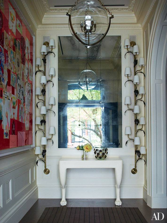 большое зеркало в вестибюле украшено разными светильниками