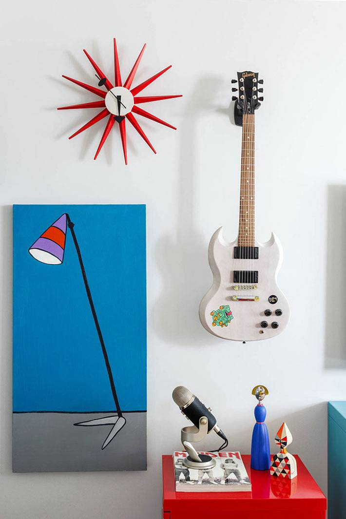 яркие картины и гитара на белой стене в комнате