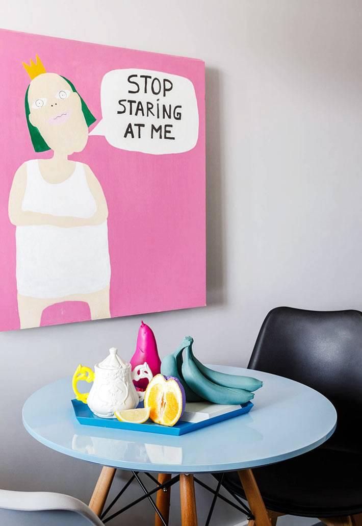 круглый стол голубого цвета и розовая картина на стене