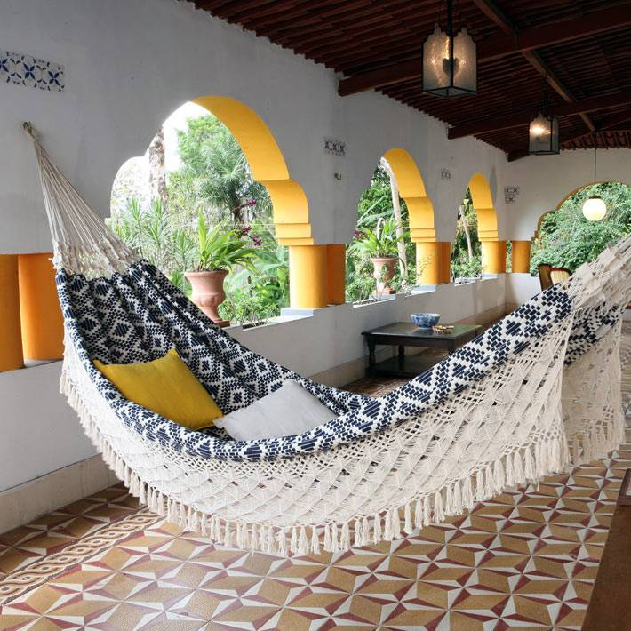 плотный гамак с яркими подушками подвешен на веранде дома