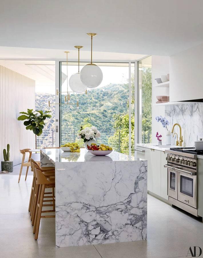 мраморный остров на кухне с окнами в пол фото
