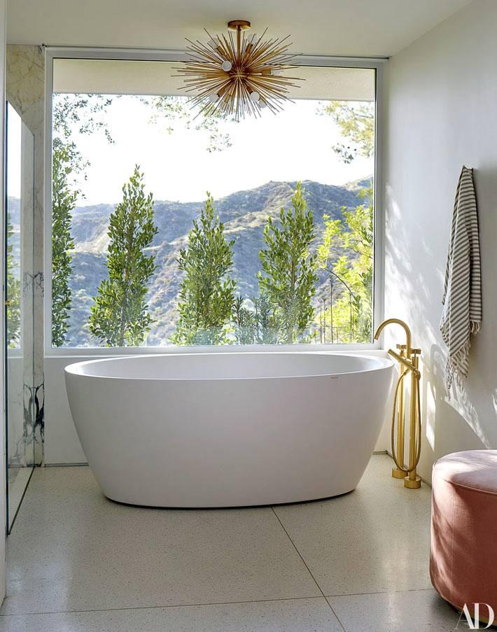 овальная чаша ванны возле окна с прекрасным видом на горы