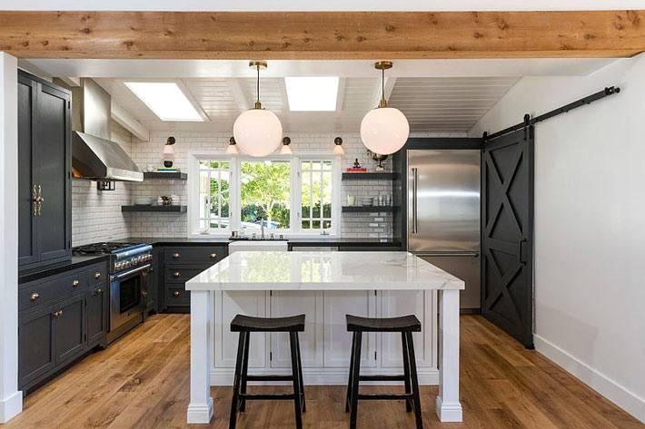 большая черная дверь в белом интерьере кухни