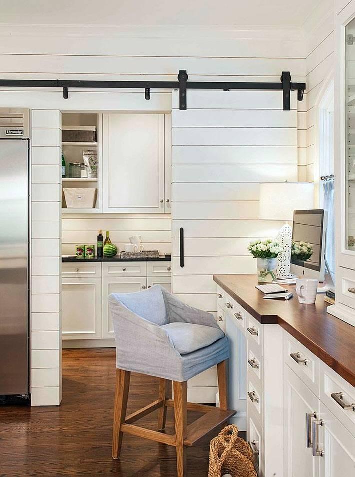 белая амбарная дверь служит зонированием кухонного пространства