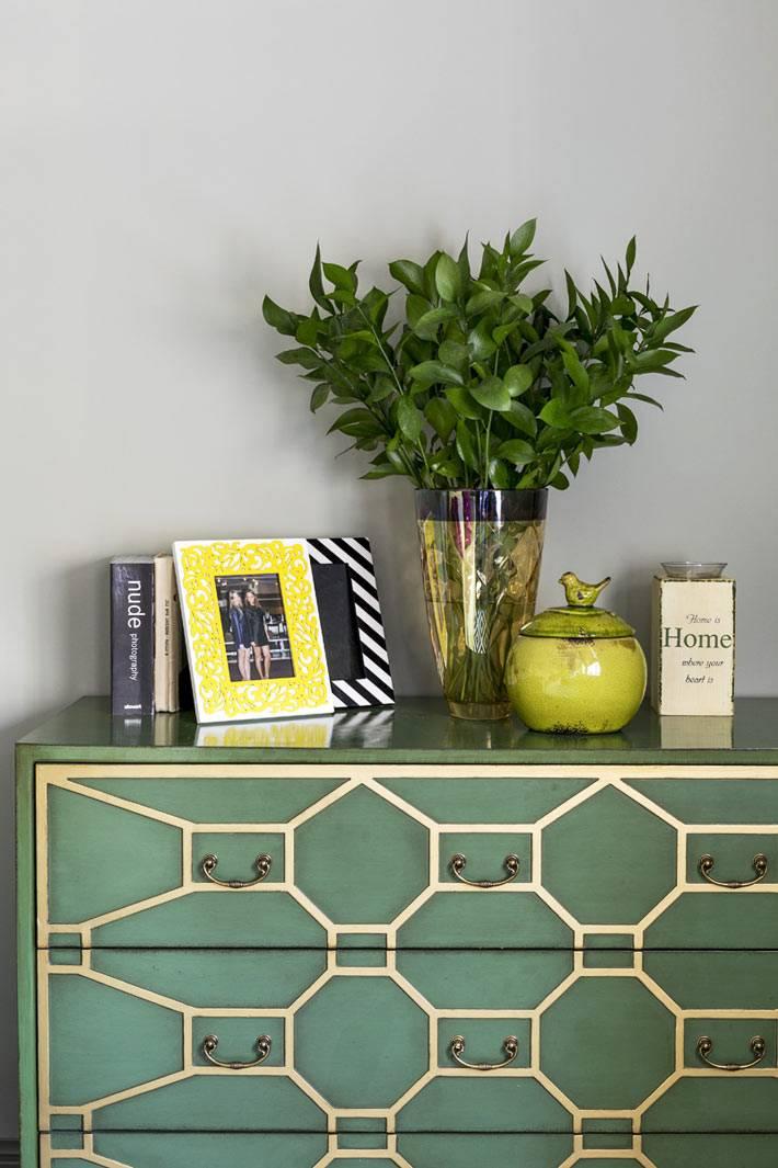 красивый зеленый комод с узором украшает комнату
