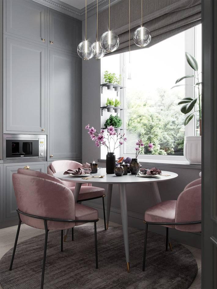круглый обеденный стол с пудровыми креслами возле окна кухни