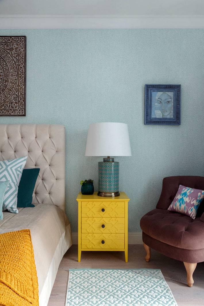 желтая прикроватная тумба в спальне с голубыми обоями