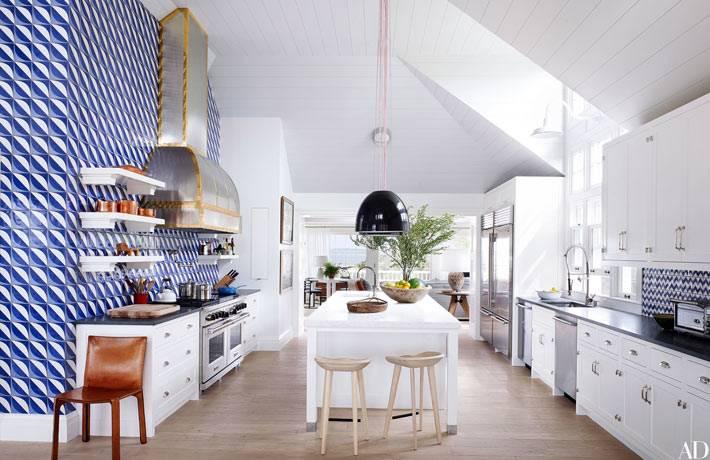 белая кухня с пестрыми синими обоями находится в мансарде дома