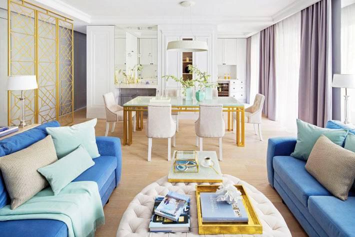 большая светлая гостиная с золотистыми элементами декора фото