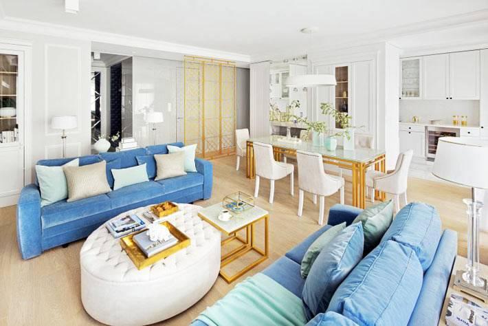 белая круглая оттоманка между синих диванов в красивой квартире
