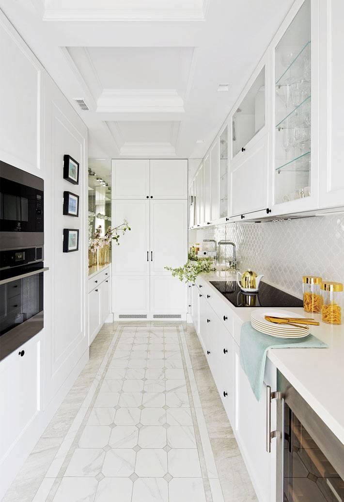 длинная узкая кухня белого цвета с кухонной мебель. по сторонам