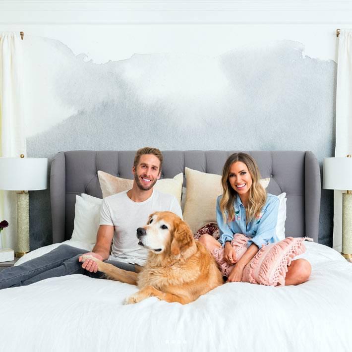 кровать для двоих с большим мягким серым подголовником
