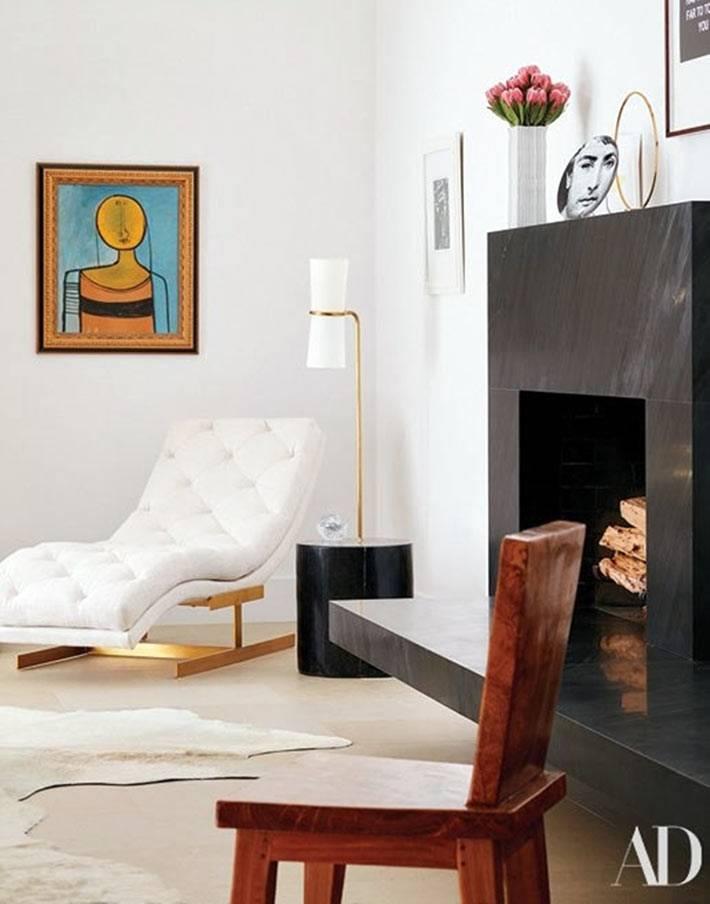 белое кожанное кресло с торшером стоят в углу возле камина