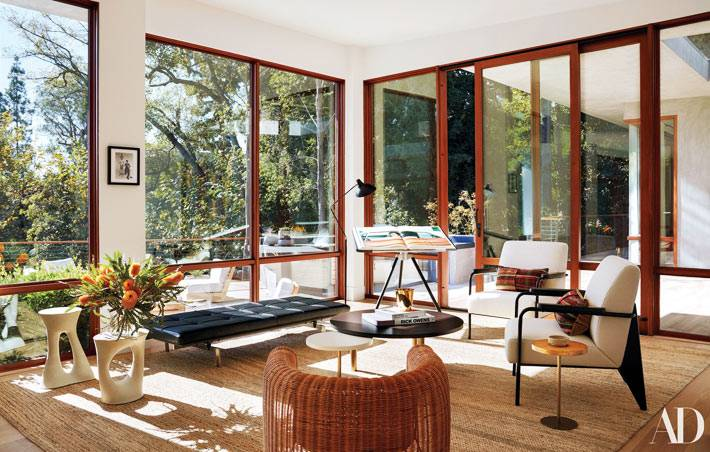 гостиная комната полностью со стеклянными стенами и видом на сад