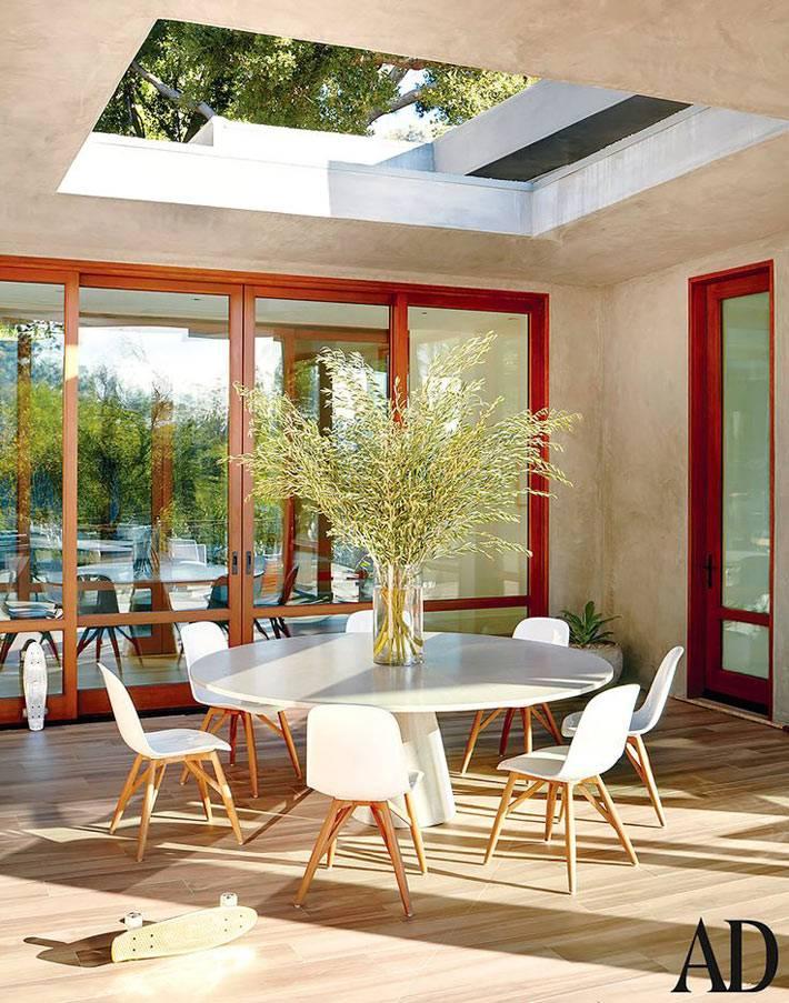 красивый белый круглый стол со стульями на террасе дома