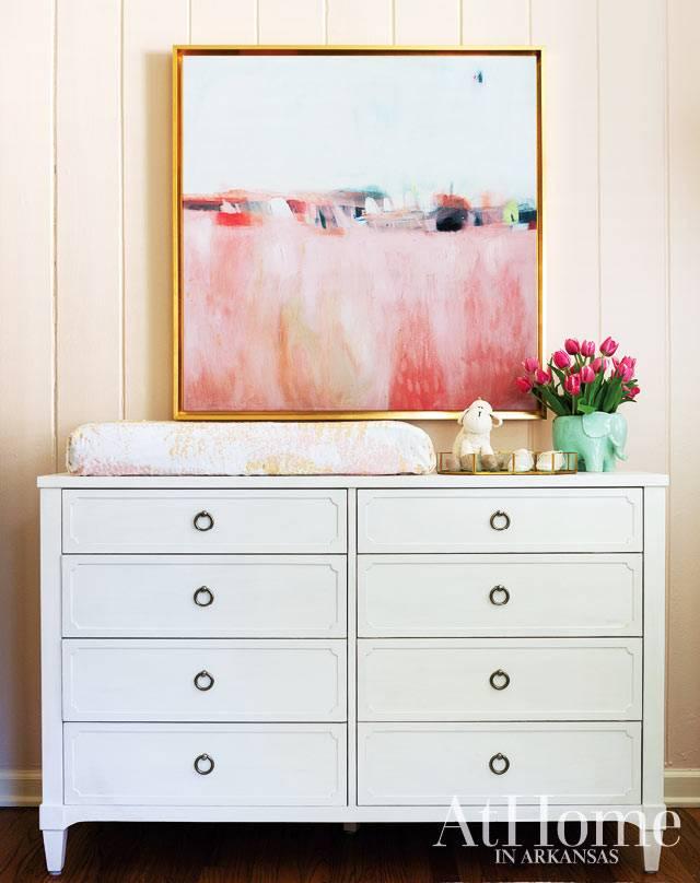 яркая картина на стене над белым комодом с ящиками в детской