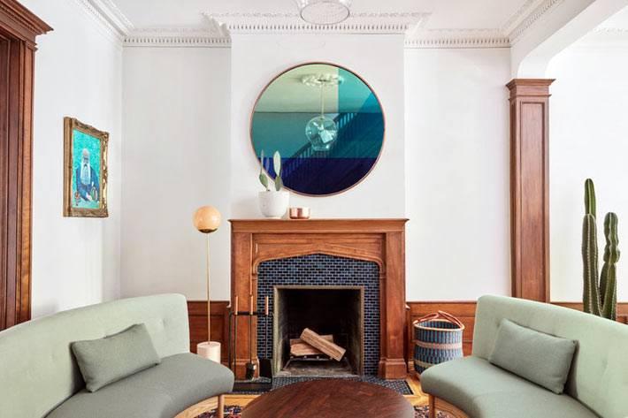 в каминной комнате стоят закругленные диваны и круглый журнальный стол