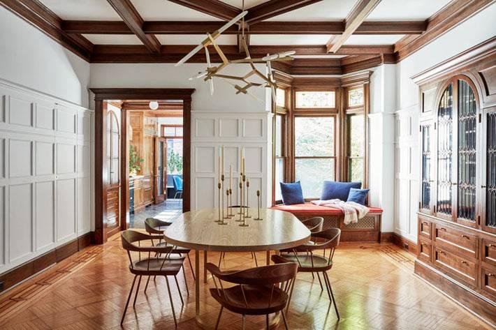 на стенах столовой деревянные панели, выкрашенные в белый цвет