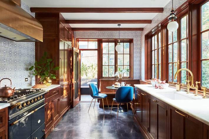 кухня роскошная с множеством окон и коричневой мебелью фото