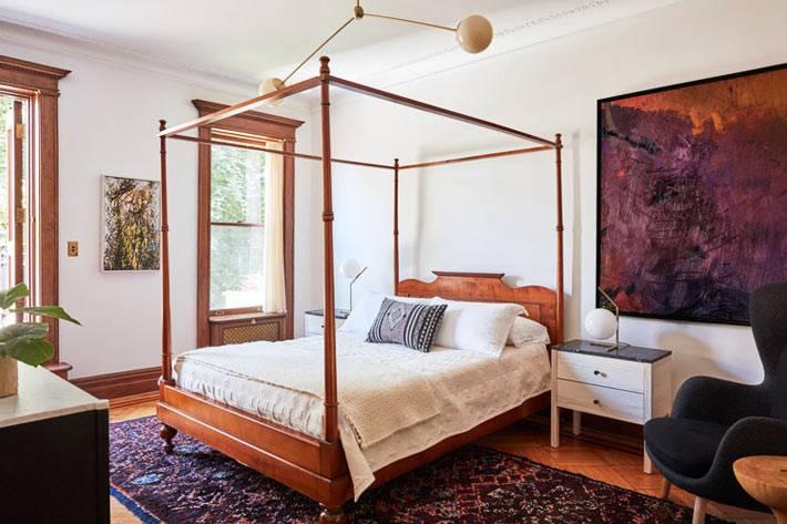 кровать с рамой для балдахина и большая картина на стене спальни