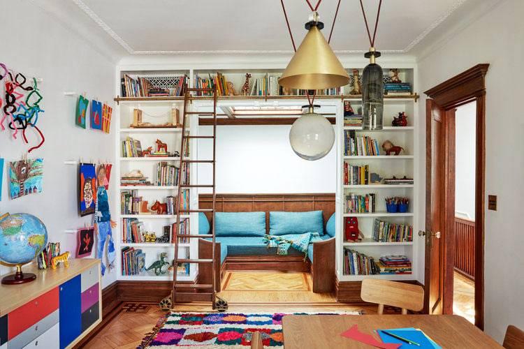 полки с книгами и мягкий диван в игровой детской комнате