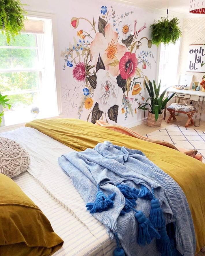 на белой стене спальни красиво смотрится роспись из цветов