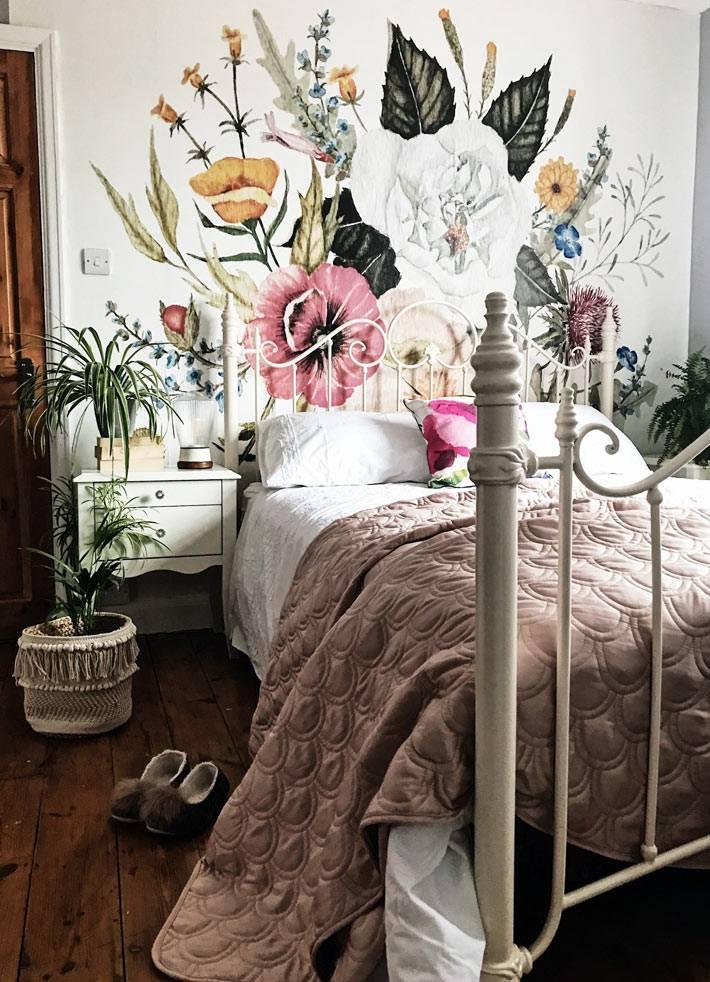 белая металлическая кровать в женской спальне с нарисованными цветами на стене