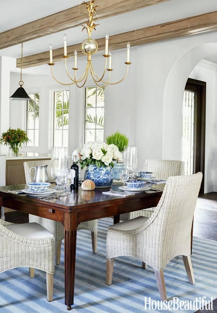 белые ротанговые стулья за коричневым обеденным столом