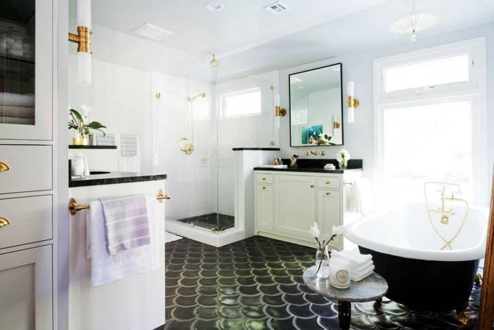 красивая черная чаша ванной на ножках с золотым краном