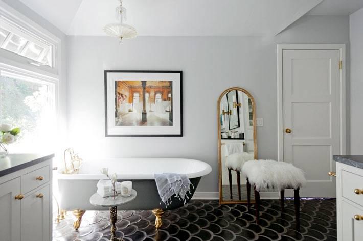 большое напольное зеркало в золотой раме возле стены ванной комнаты