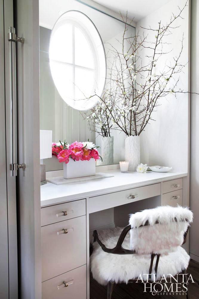 женский туалетный столик под круглым окном в ванной комнате