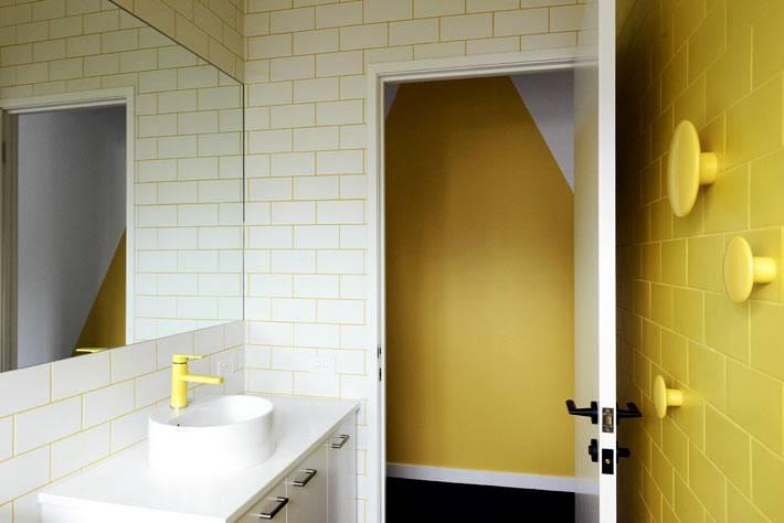солнечный интерьер ванной комнаты с желтой затиркой швов на белой плитке