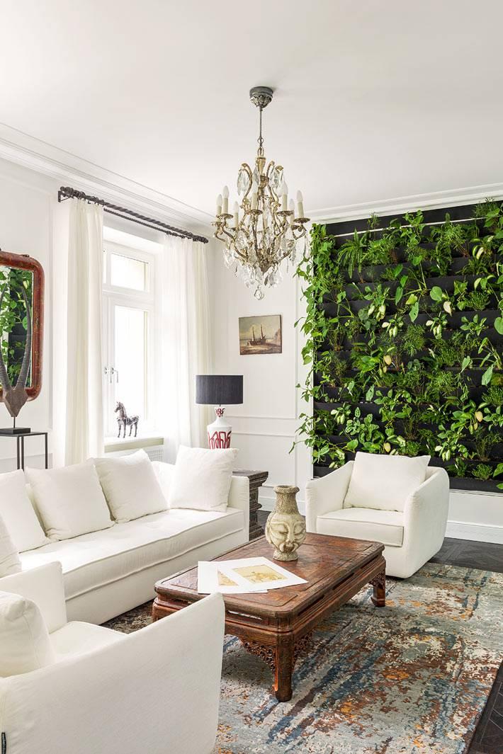 зеленая фитостена в комнате с белыми стенами и хрустальной люстрой фото