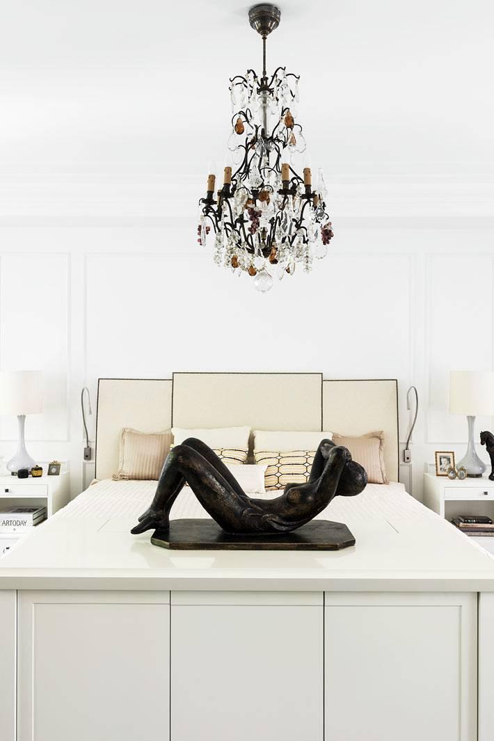 хрустальная люстра над кроватью в белом интерьере спальни