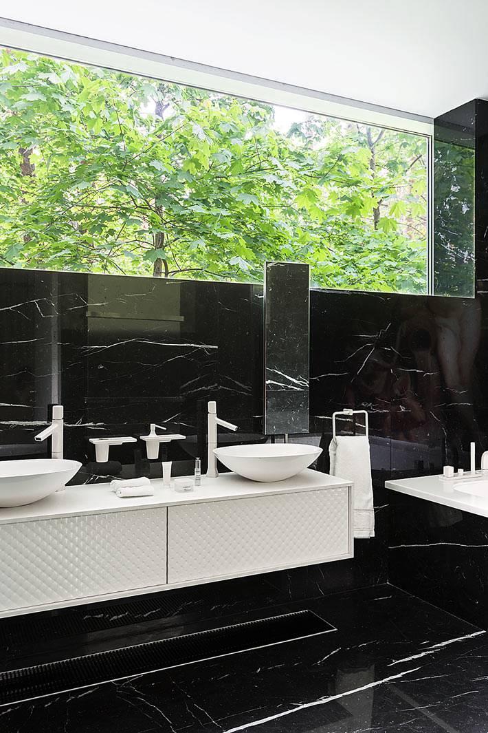 красивая современная ванная комната выложена черной мраморной плиткой